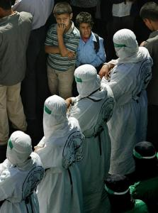 Young Palestinian boys watch militants from Hamas dressed as suicide bombers pray during the funeral of Tariq Abu Hussein, the leader of the militant wing of Hamas in Rafah, at the Al Awdah Mosque in the the Rafah refugee camp, southern Gaza Strip (news - web sites), Saturday Oct. 18, 2003. Hussein was killed during clashes with Israeli troops during an incursion in the Salam neighborhood Saturday. For more than a week, Israel's military has been operating in the southern Gaza town of Rafah in what the army says is an operation to find and destroy tunnels used by Palestinians to smuggle weapons across the Egyptian border into Gaza. (AP Photo/Kevin Frayer)