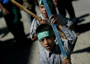 Palestinian boys wearing Hamas headbands march during the funeral of Shadi Saqer, 18, in the Rafah refugee camp, southern Gaza Strip (news - web sites), Friday Oct. 17, 2003. Saqer died Thursday of wounds he received from Israeli troops during an incursion in the Yebena neighborhood last week. (AP Photo/Kevin Frayer)